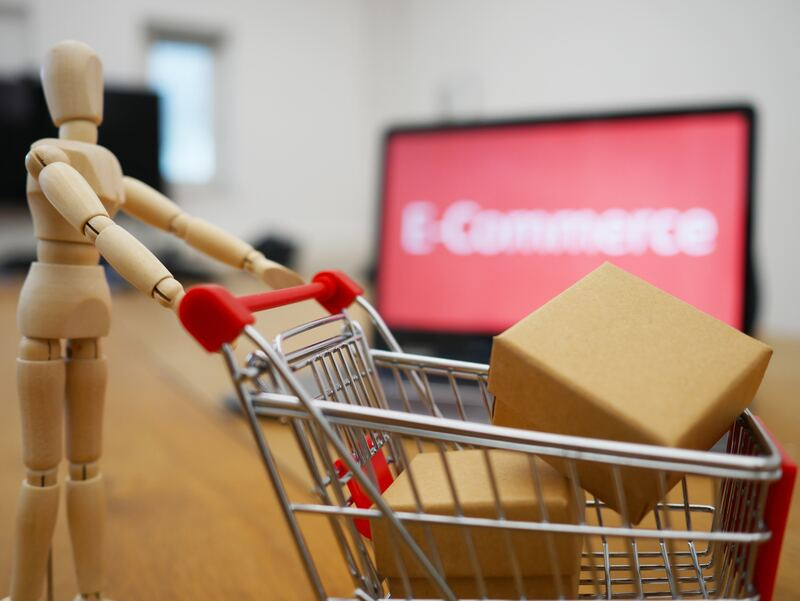 Small wooden manikin toy pushing a shopping car with packages in front of a laptop with the word e-commerce on it screen, blurred in the background