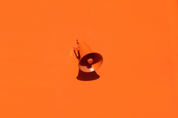 Orange megaphone on orange wall by Oleg Laptev