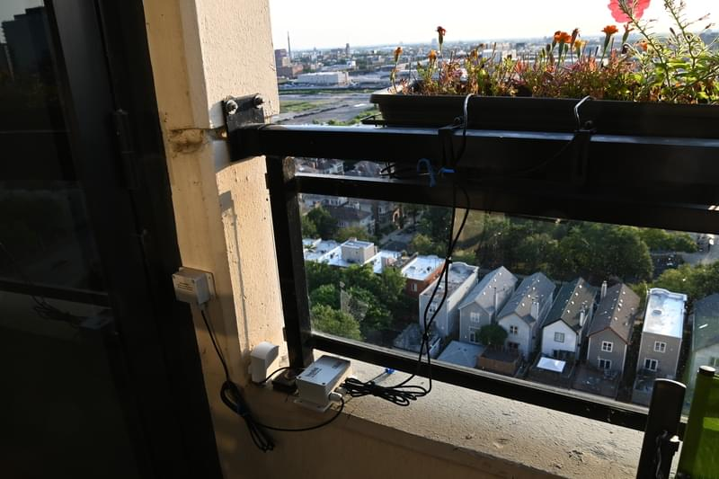 Photo of flower planters hanging from balcony railing with electronic sensors attached