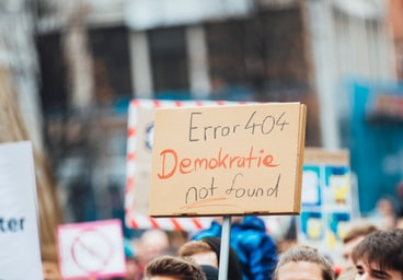 Protester holding sign saying 'Error 404 Demokratie not found'